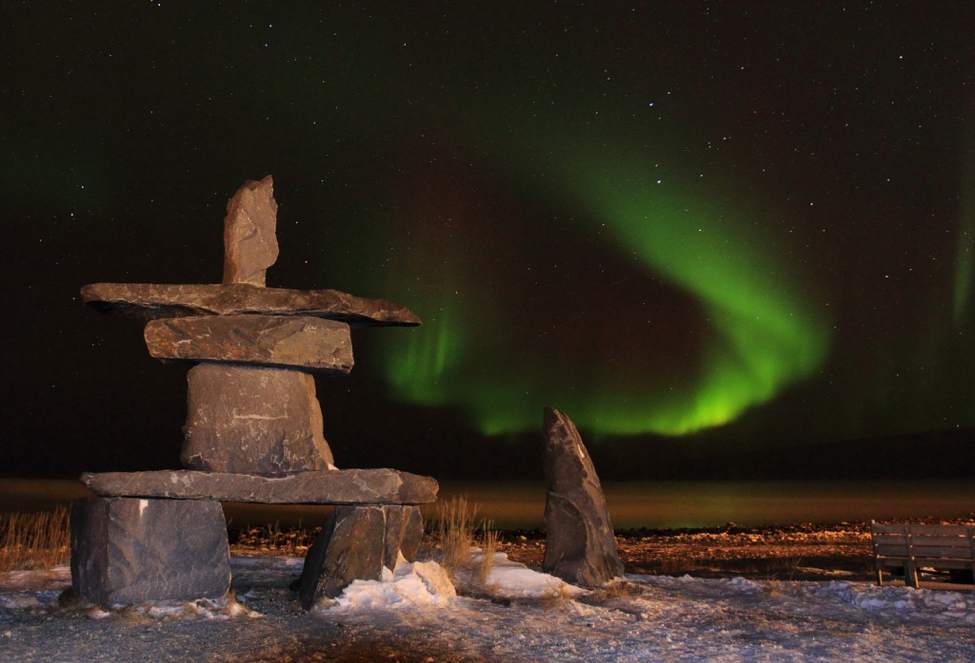 An inukshuk on Hudson Bay, Canada with the Aurora Borealis in the background. Copyright Brad Josephs/NHA