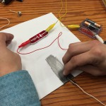 Paper, pencil, alligator clips, and lightbulb from snap circuit